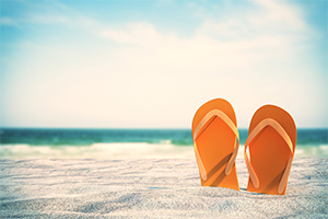 Stock photo of sandals in the sand at a beach.